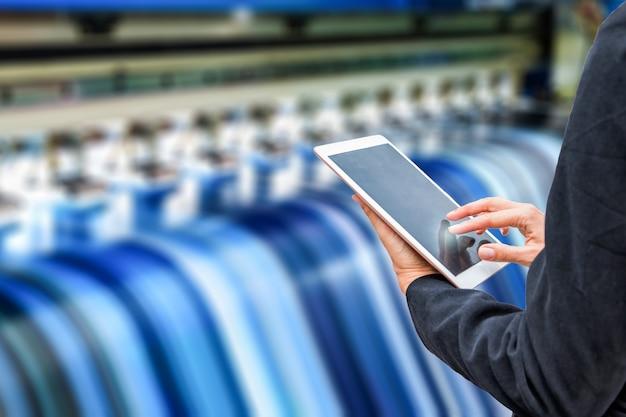 Técnico que usa o controle da tabuleta com o vinil azul da impressão a jacto de tinta grande do formato
