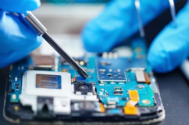 Técnico reparando micro circuito de smartphone