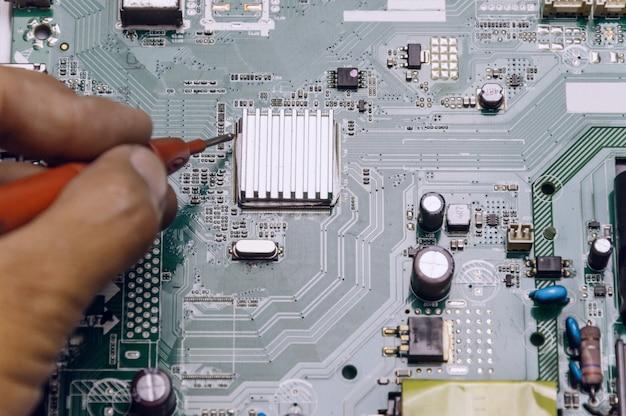 Técnico reparando placa de televisão, engenheiro mede a voltagem na placa de televisão