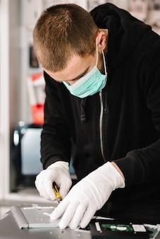 Técnico reparando um laptop no laboratório. homem que trabalha, usando máscara protetora na oficina.