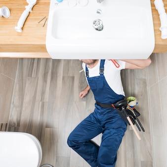 Técnico sanitário deitado sob pia