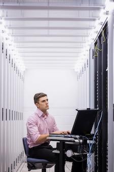 Técnico sentado na cadeira giratória usando laptop para diagnosticar servidores