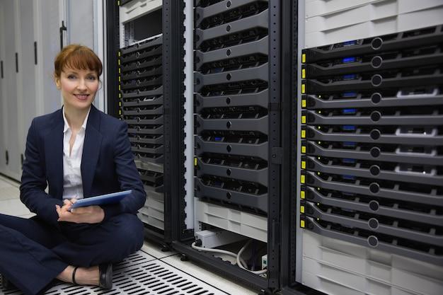 Técnico sentado no chão ao lado da torre do servidor usando o tablet pc