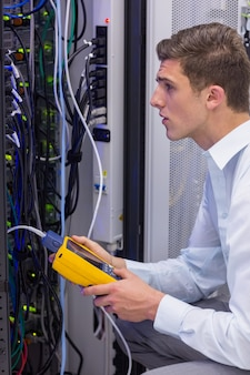 Técnico sério usando analisador de cabo digital no servidor