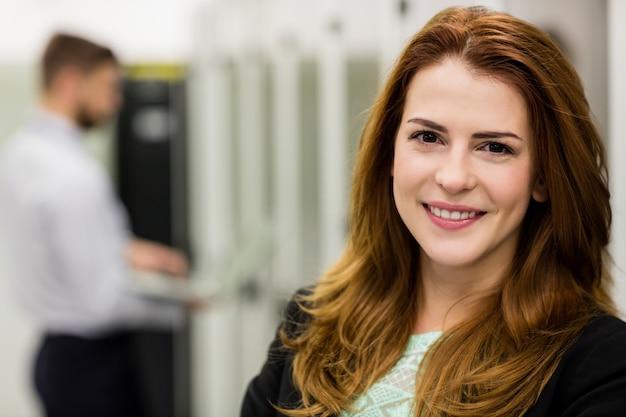 Técnico sorridente em pé em uma sala de servidores