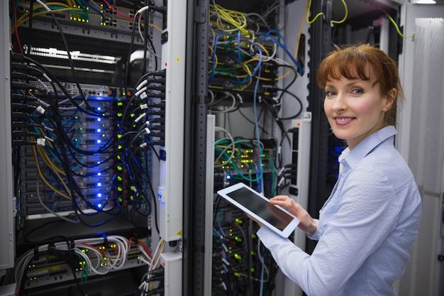 Técnico sorridente usando tablet pc enquanto analisa o servidor