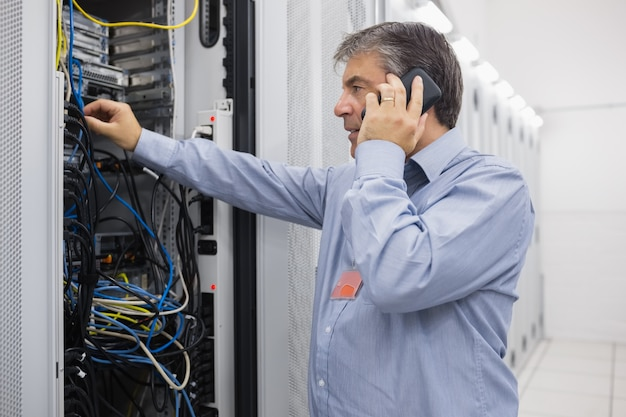 Técnico telefonando ao reparar o servidor
