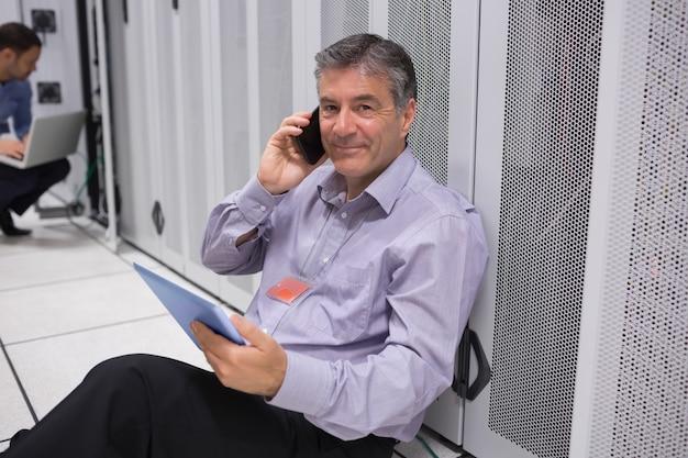 Técnico telefonando no chão com tablet digital