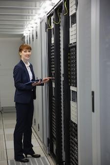 Técnico trabalhando em servidores usando tablet pc