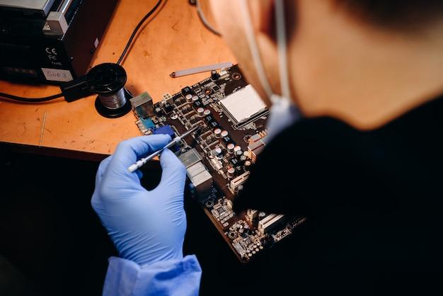 Técnico trabalhando no conserto de um computador em laboratório