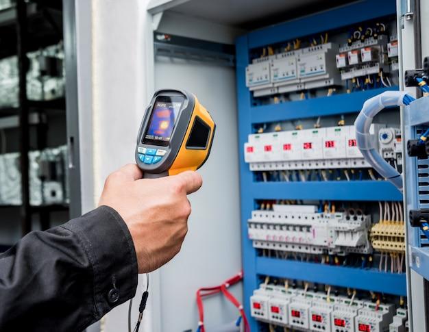 Técnico usa câmera de imagem térmica infravermelha para verificar a temperatura na caixa de fusíveis