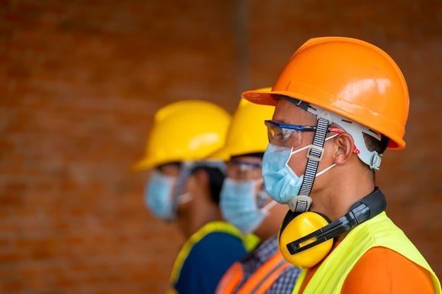 Técnico usa máscaras de proteção de segurança para a doença de coronavírus 2019 (covid-19) na fábrica industrial de máquinas, o coronavirus se transformou em uma emergência global.
