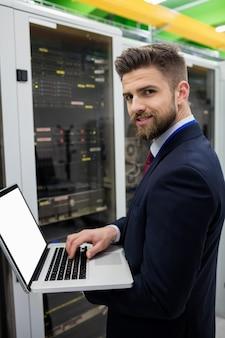 Técnico usando laptop enquanto analisa o servidor