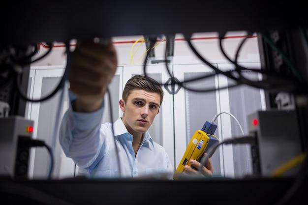 Técnico usando o testador de cabos ao consertar o servidor