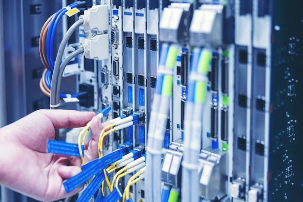Técnico usando tablet digital na sala do servidor, conserta placa-mãe da placa, verificando o status do link de rede