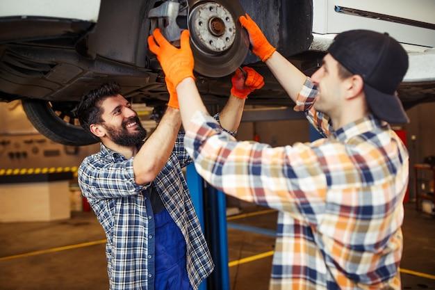 Técnicos caucasianos trabalhando no pneu do carro levantado no moderno centro de serviços