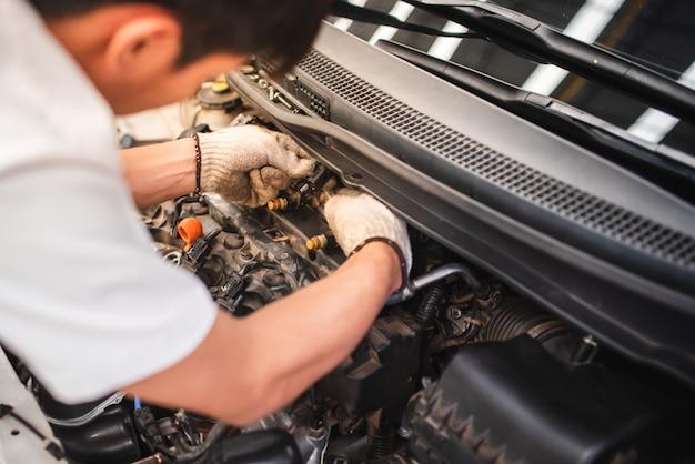 Técnicos de automóveis estão verificando sistemas de injeção de automóveis usando ferramentas de diagnóstico e reparo na casa de máquinas para veículos a motor.