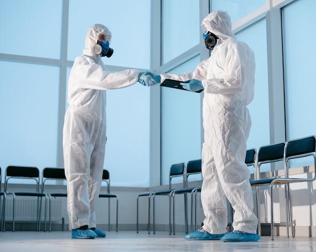 Técnicos de laboratório em trajes de proteção apertando as mãos