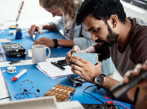 Técnicos elétricos trabalhando em peças eletrônicas