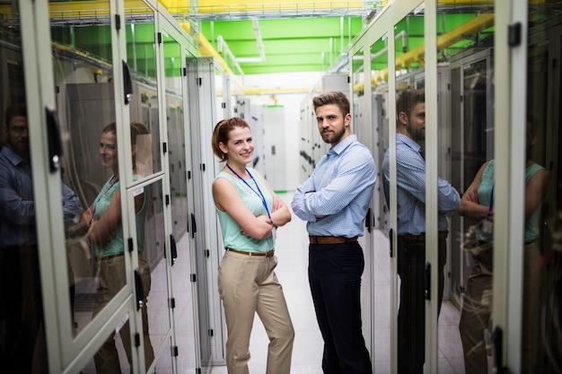 Técnicos em pé com os braços cruzados em uma sala de servidores