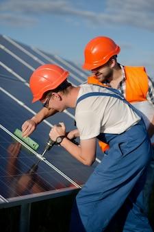 Técnicos instalando painéis fotovoltaicos na estação de energia solar.