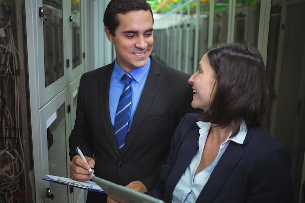 Técnicos interagindo entre si enquanto analisam o servidor