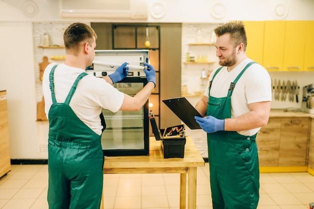 Técnicos uniformizados consertam geladeira em casa