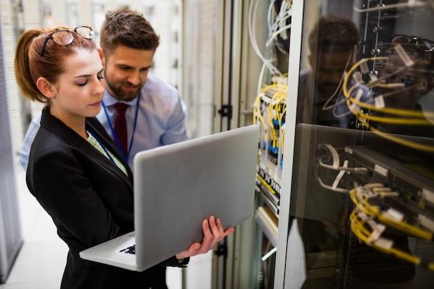 Técnicos usando laptop enquanto analisam o servidor