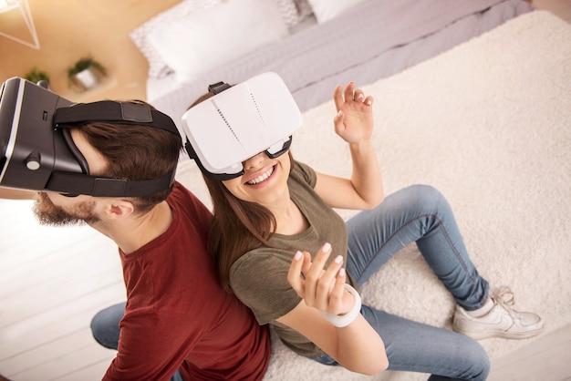 Tecnologia avançada. vista superior de uma mulher alegre e otimista levantando as mãos enquanto sorri e se diverte com óculos de realidade virtual