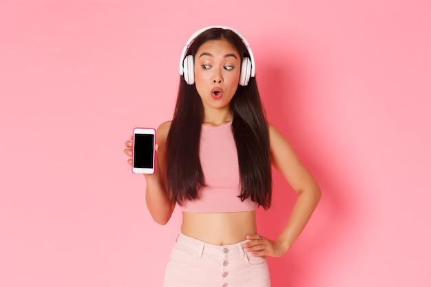 Tecnologia, comunicação e conceito de estilo de vida online. excitada e feliz menina asiática parecendo espantada, mostrando a tela do smartphone enquanto ouve podcast ou música em fones de ouvido, parede rosa.