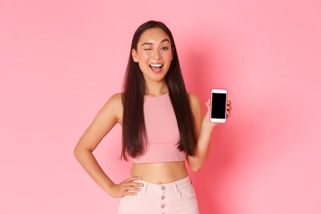 Tecnologia, comunicação e conceito de estilo de vida online. retrato de menina asiática coquete piscando para incentivar o download do aplicativo, verifique o podcast ou loja da internet, mostrando a tela do smartphone.