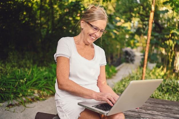 Tecnologia, conceito de pessoas de idade avançada - idosa feliz sênior velha trabalhando online com o computador portátil ao ar livre no jardim. trabalho remoto, educação a distância.