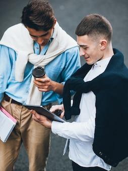 Tecnologia da informação. diversão de lazer moderno. caras metrossexuais assistindo conteúdo divertido no tablet.