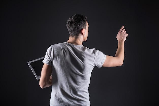 Tecnologia da informação. especialista em ti bonito e inteligente em pé na frente da tela sensorial e usando-a enquanto tem um laptop na mão