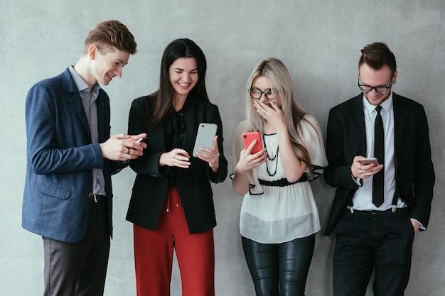 Tecnologia da informação. estilo de vida moderno. jovens colegas em pé, usando smartphones e internet para compartilhar conteúdos divertidos.