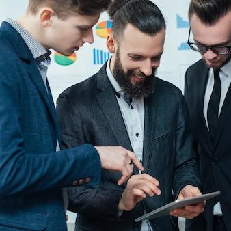 Tecnologia da informação nas empresas modernas. era digital. equipe masculina jovem usando tablet na reunião corporativa.