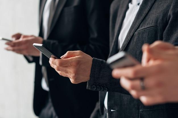 Tecnologia da informação no mundo corporativo moderno. foto recortada de homens de negócios em pé na fila com smartphones.