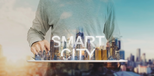 Tecnologia de cidade inteligente, um homem usando tablet digital e holograma de edifícios modernos