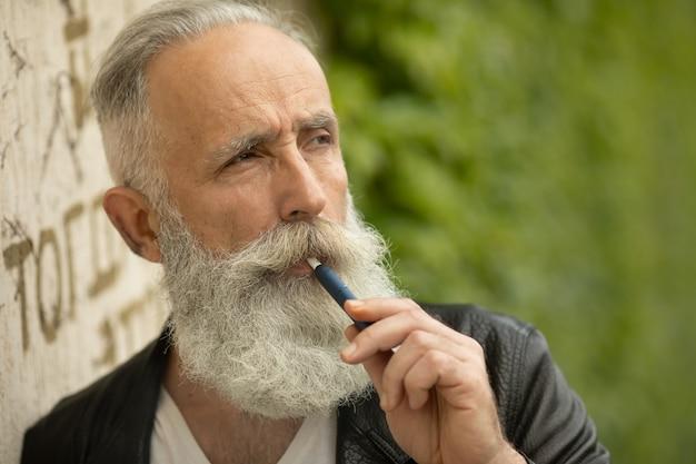 Tecnologia de cigarro eletrônico. sistema iqos de tabaco. close-up de um homem barbudo sênior fumando um cigarro híbrido elétrico com uma almofada de aquecimento.