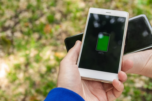 Tecnologia de compartilhamento de carga sem fio da bateria do telefone. as pessoas compartilham sua carga de smartphone sem fio no parque.