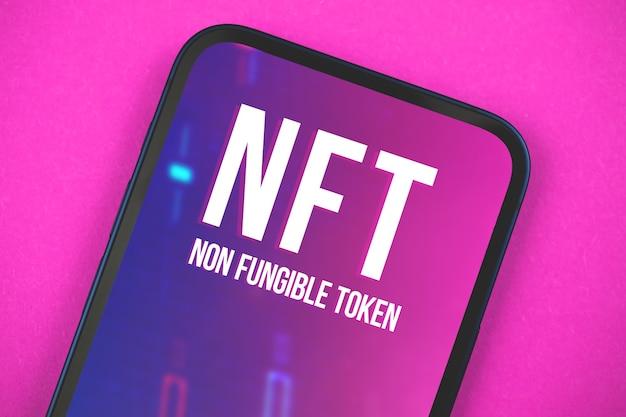 Tecnologia de cyptoart nft, logotipo na tela do telefone móvel moderno, conceito futuro de criptomoeda e blockchain, fundo roxo e foto da vista superior