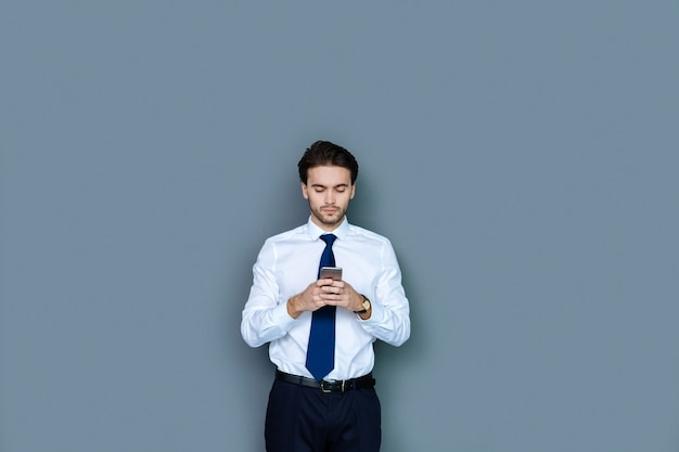 Tecnologia digital. homem de negócios inteligente simpático e bonito em pé e usando seu smartphone enquanto digita uma mensagem