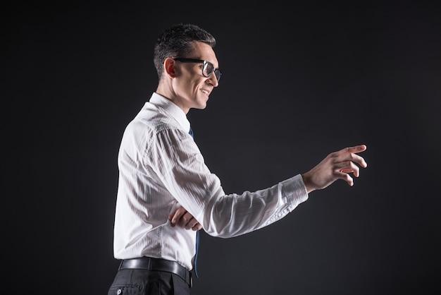 Tecnologia do futuro. homem alegre e feliz inteligente usando óculos e sorrindo enquanto usa o painel do computador