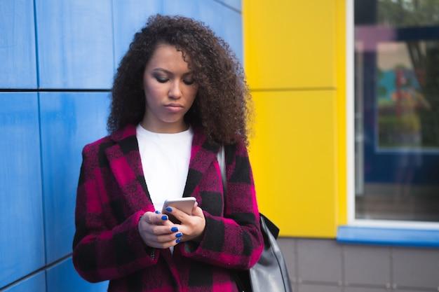 Tecnologia e comunicação. mulher adolescente infeliz enviando mensagens de texto no celular usando smartphone lendo sms no azul