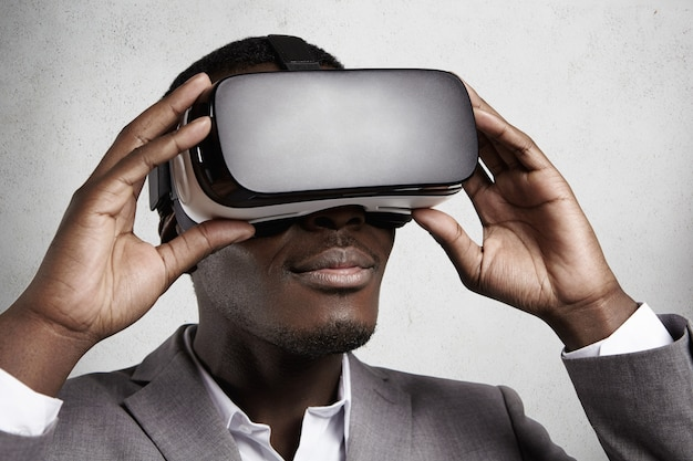 Tecnologia e entretenimento. trabalhador de escritório bem sucedido de pele escura em elegante terno cinza experimentando realidade virtual usando óculos de fone de ouvido vr.