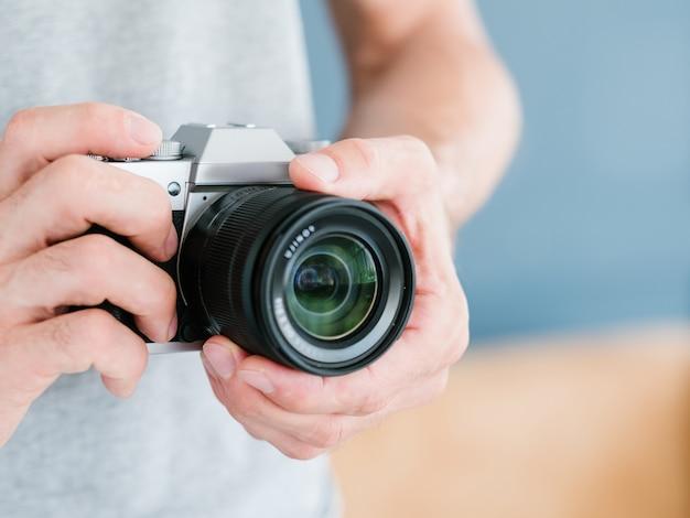 Tecnologia eletrônica moderna para a criação de belas fotos. homem irreconhecível, segurando a câmera fotográfica nas mãos.