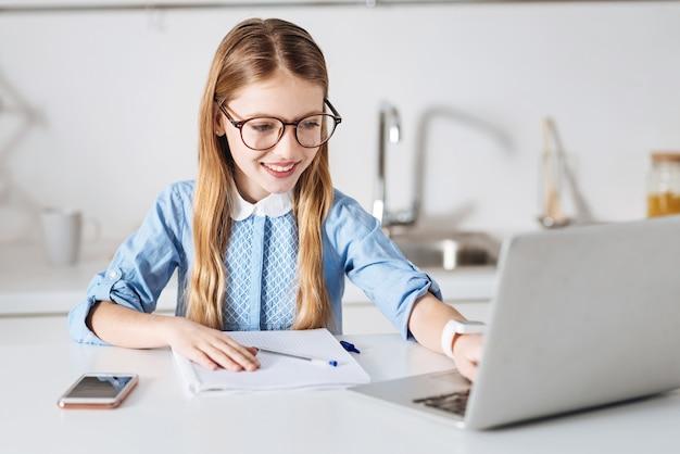 Tecnologia em uso. aluna inteligente e focada trabalhando em sua redação e procurando algumas dicas online enquanto está sentada à mesa em uma cozinha iluminada pelo sol