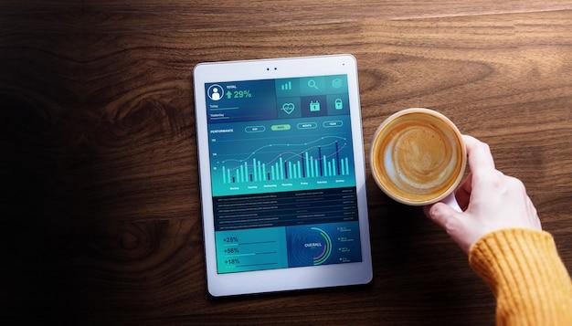 Tecnologia, finanças e marketing de negócios no conceito de vida cotidiana. a mulher com café quente que vê gráficos e cartas mostra na tabuleta de digitas. vista do topo