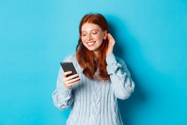 Tecnologia. garota ruiva feliz olhando satisfeita com o telefone celular, lendo elogios na mensagem, sorrindo e prender o cabelo atrás da orelha, vestindo um suéter sobre fundo azul.