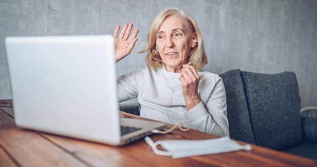 Tecnologia, idade avançada e conceito dos povos - mulher superior mais idosa feliz com a máscara médica da cara que trabalha e que faz uma videochamada com laptop em casa durante a pandemia do coronavírus covid19. ficar em casa